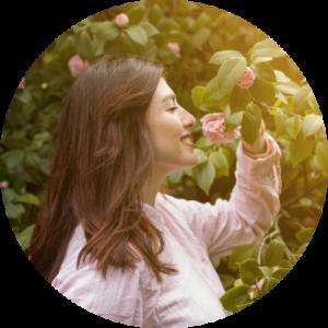 mulher feliz cheirando uma flor