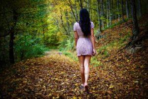 Mulher descalça caminha numa trilha em meio a natureza.