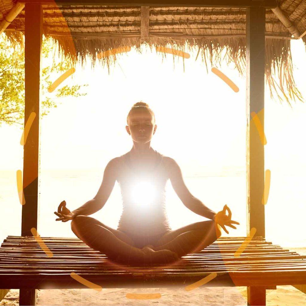 mulher sentada em pose de meditação, criando um forte campo energético de proteção a sua volta, que irradia uma luz dourada a partir do chackra cardíaco