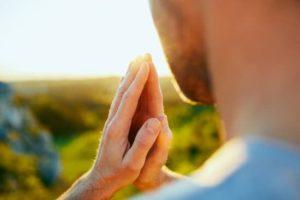 Homem de costas em oração, criando um campo energético de proteção, que impede a implantação de ovoides.