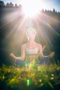 Mulher sentada na grama, em concentração, descarregando energias densas no solo, e recebendo as energias curativas do sol.