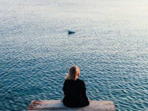 mulher-sentada-ponte-perto-do-mar